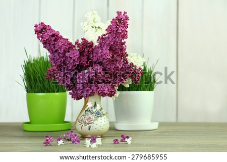 lilacs in a vase on a wooden background - stock photo