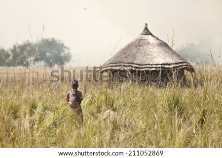 LILIIR, SOUTH SUDAN-DECEMBER 4 2010, Unidentified child stands in field with grassfires in the background in the village of Liliir, South Sudan. - stock photo