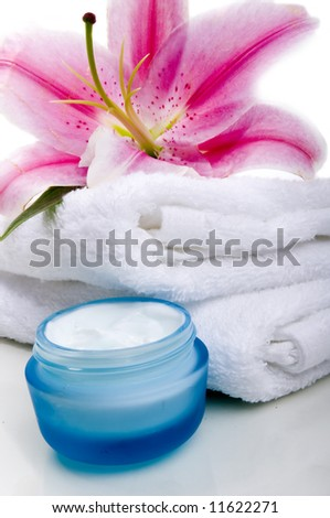 Lilly flower on white towel  with face cream - stock photo
