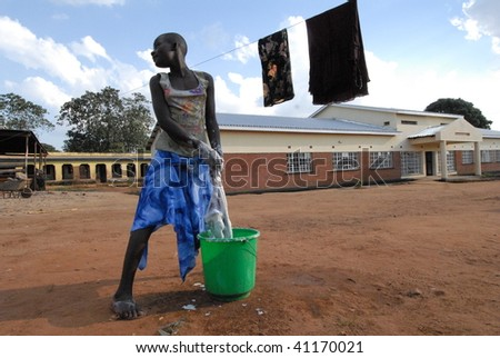LILONGWE, MALAWI - MAY 30: An orphan washing clothes outside of the Chisom orphanage in Lilongwe Malawi on May 30, 2008. - stock photo