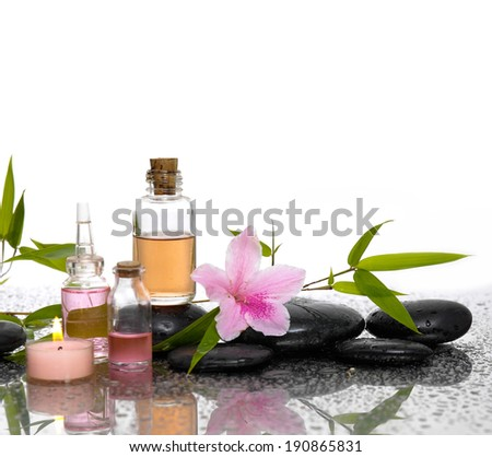 Lily flower and burn candles ,black stones, oil ,leaf on wet background - stock photo
