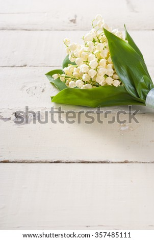 lily of the valley flowers on bright wood table