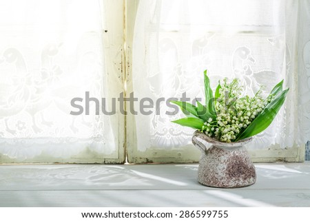 Lily of the valley in a vase near a sunny window