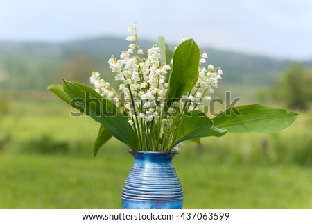 Lily of the valley in blue vase in France - stock photo