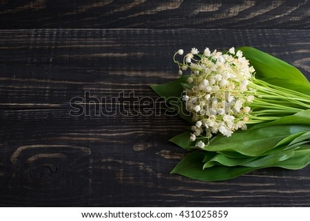 Lily of the valley on a wooden background in daytime