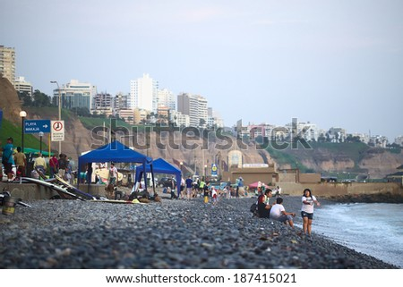 LIMA, PERU - APRIL 2, 2012: Unidentified people on the rocky Pacific coast of Miraflores on April 2, 2012 in Lima, Peru. On the steep coast the modern residential buildings of Miraflores can be seen.  - stock photo