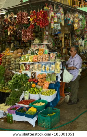 LIMA, PERU - FEBRUARY 13, 2012: Unidentified person at fruit and vegetable stand on the market called Mercado No 1 de Surquillo on February 13, 2012 in Lima, Peru.  - stock photo