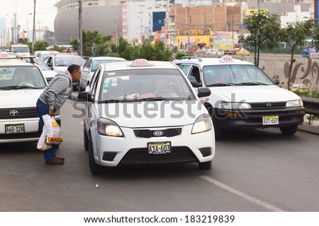 LIMA, PERU - JULY 21, 2013: Unidentified man asking a taxi for the fare on Av. Paseo de la Republica in the city center on July 21, 2013 in Lima, Peru. In Lima, taxi fares are agreed upon beforehand. - stock photo