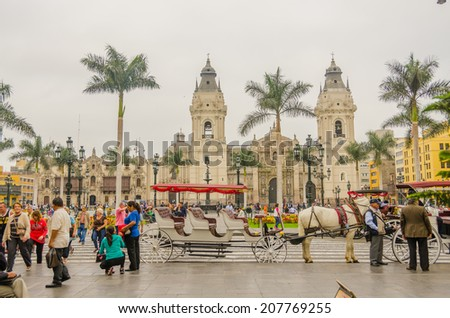 LIMA, PERU, MAY 23, 2014 - Horse drawn carriage waits for tourists in Plaza Mayor with Cathedral de Lima in background - stock photo