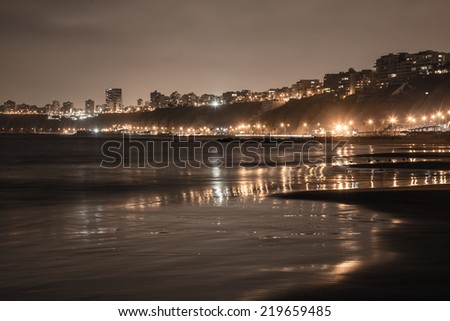 LIMA, PERU: Night shot of  reflection of the city lights over the sea in the beach.