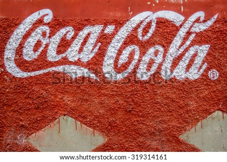 LIMA, PERU - OCTOBER 10, 2014 : Coca Cola trademark letters written on a rough red wall, seen in Lima, Peru