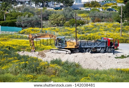 LIMASSOL,CYPRUS - MARCH 19, 2013:Yellow excavator load earth on truck in a construction site in Limassol,Cyprus on March 19, 2013 - stock photo