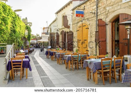 LIMASSOL, CYPRUS - 30 MAY 2014: An alley in the historic medieval city center of Limassol in Cyprus. A view of the cafe, restaurant, cypriot taverna, tables and the souk leading to the castle square - stock photo