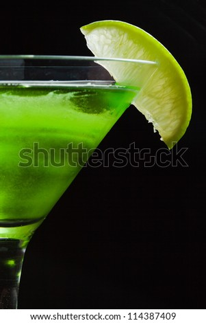 Lime and melon martini cocktail detail on black background - stock photo