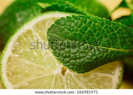 Lime and mint on wooden  background - stock photo