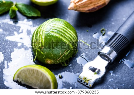 Lime and zest, natural refreshing ingredients on dark slate. - stock photo