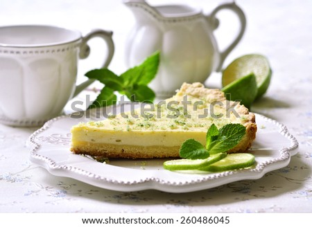 Lime cheesecake with mint sugar on a white plate. - stock photo