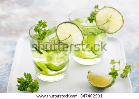 Lime, cucumber, parsley cocktail, lemonade, detox water with ice cubes in a glasses on a white plate - stock photo