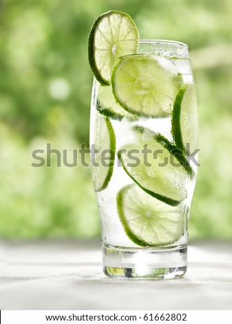 lime drink with ice, on a table with green background - stock photo