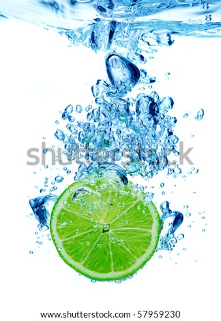 Lime dropped in a water - stock photo