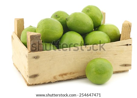 lime fruits in a wooden crate on a white background