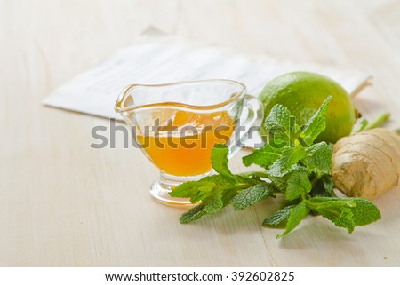 Lime, ginger, honey and mint on a white wooden table