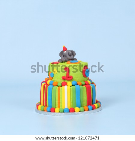 Lime green elephant cake on blue seamless background with red, blue, white and orange stripes and polka dots - stock photo
