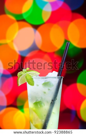 lime in a glass of mojito with ice on bokeh background - stock photo