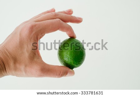 Lime in her hand on a white background closeup
