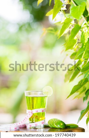 Lime juice healthy fruit and tape measure placed on the table in the morning. - stock photo