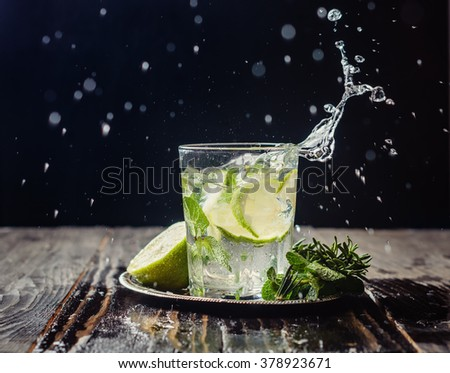 lime lemonade with rosemary and ice on a dark background in glass transparent glass. drink in motion, spray, motion - stock photo
