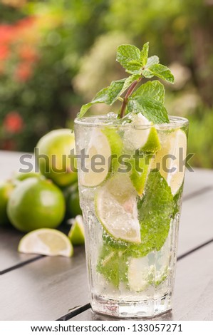 Lime Mojito cocktail on wooden table outdoor close up, a Cuban cocktail made with cuban rum, lime, sugar and a splash of soda - stock photo