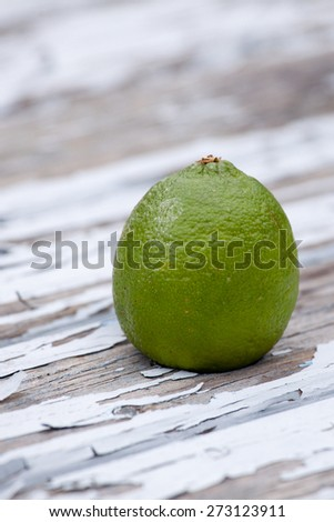 lime on a wooden table with blue flaking paint - stock photo