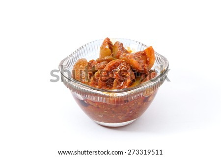 lime or mango pickle in a glass bowl isolated on white background