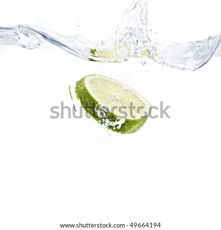 lime slice splashing into water with white background - stock photo