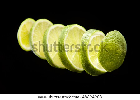 lime sliced and lined up on black background - stock photo