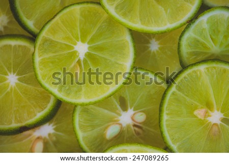Lime slices background in green - stock photo