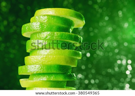 Lime slices heap over defocused lights - stock photo