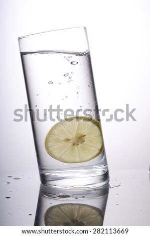 Lime splashing into glass of water ,Lemon water