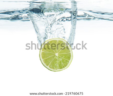 lime splashing into the water - stock photo