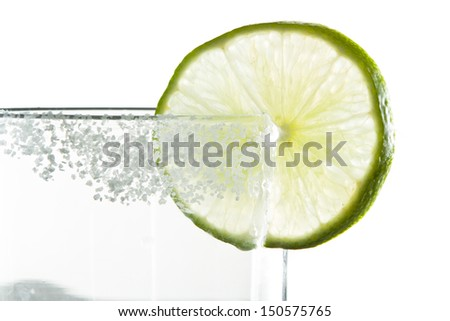 lime wheel and salt on the rim of a glass isolated on a white background - stock photo
