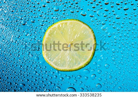 Lime with water drops isolated on blue background. - stock photo
