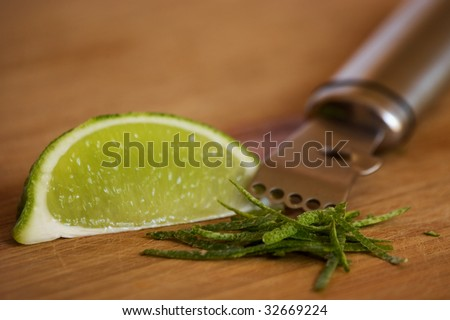 Lime zest and wedge with zester - stock photo