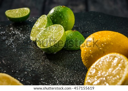 Limes and lemons citrus fruits cut in half - stock photo