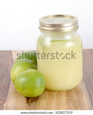 limes and limeade in a bottle