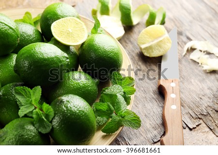 Limes and zest on wooden table - stock photo