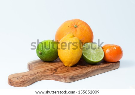 Limes, lemon, orange and tangerine on a wooden table, isolated on white