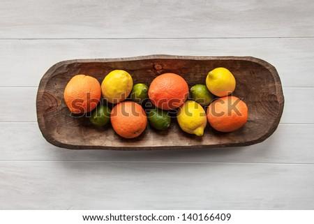 Limes, Lemons and Orange Citrus Fruit in a Vintage Wood Tray on a Whitewashed White Wood Background - stock photo