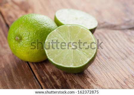 Limes on wooden background. Shallow dof - stock photo