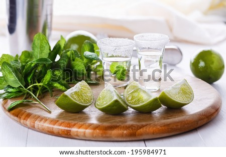 Limes quarters, mint leaves and tequila shots on a chopping board over white wooden background. Selective focus, shallow DoF - stock photo